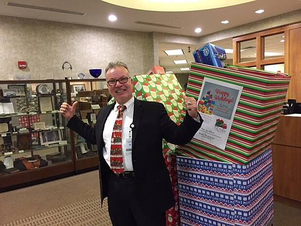 Yuletide President Chris Miller in front of Toy Truck Boxes